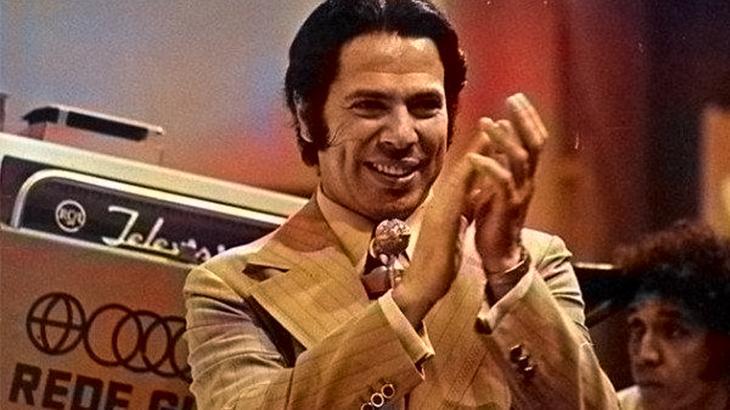 Silvio Santos no palco do seu programa na Globo batendo palmas