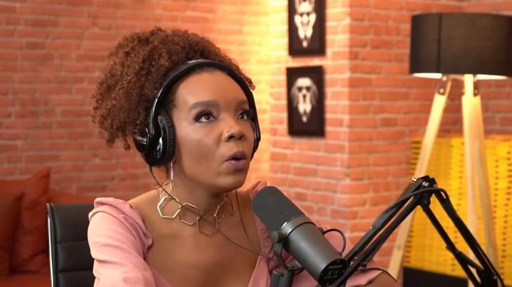 Thelma Assis com fone no ouvido falando no microfone de roupa rosa