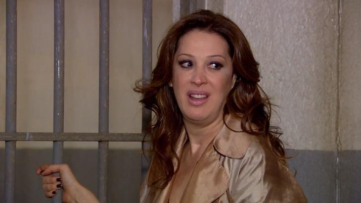 Cena de Ti Ti Ti com Jaqueline presa com a mão na cela e olhando para trás