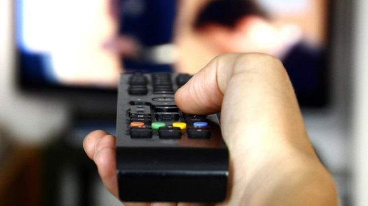 Homem com controle vendo televisão