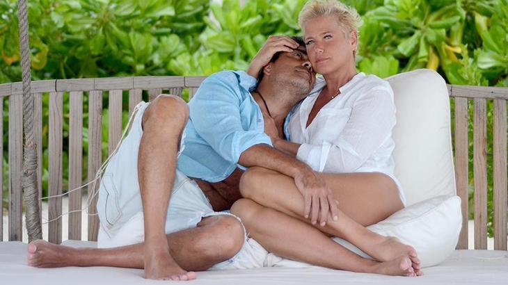 Xuxa abraçada com Junno em um banco com almofadas