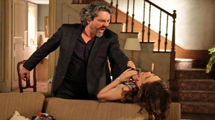 José Alfredo apertando o pescoço de Cora enquanto ela se apoia no sofá