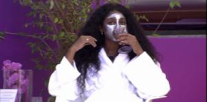 Camilla sentada de roupão e máscara no rosto