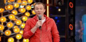 Tiago Leifert de jaqueta vermelha segurando microfone