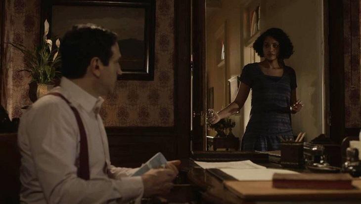 João Aranha em sua sala sentado e Shirley de pé abrindo a porta em Éramos Seis
