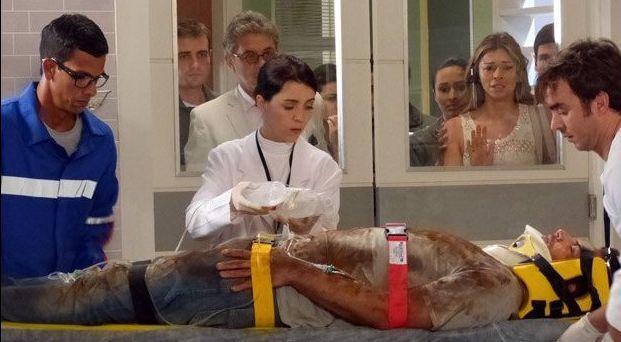 Ester, Duque e os tenentes observam pelo janela do ambulatório Cassiano  na maca, inconsciente