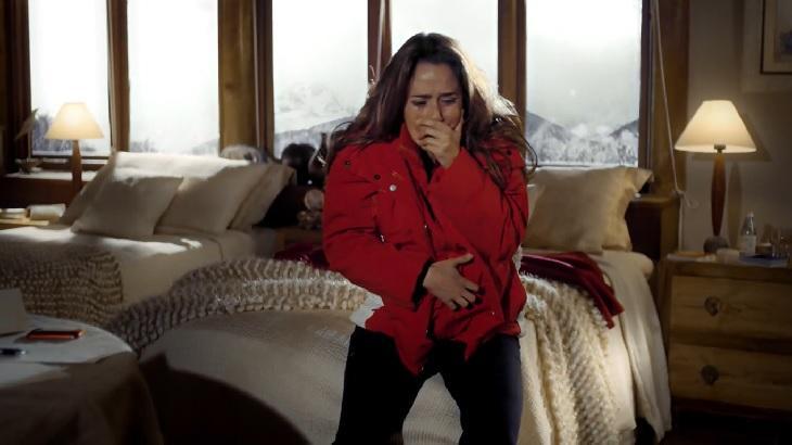 Cena de A Vida da Gente com Ana passando mal sentada com a mão na boca e outra na barriga