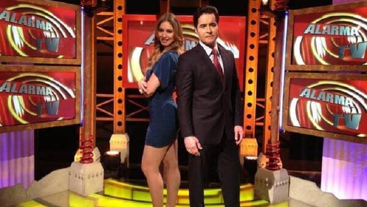 """Apresentadores do """"Alarma TV"""", de pé, lado a lado, no estúdio do programa gringo."""