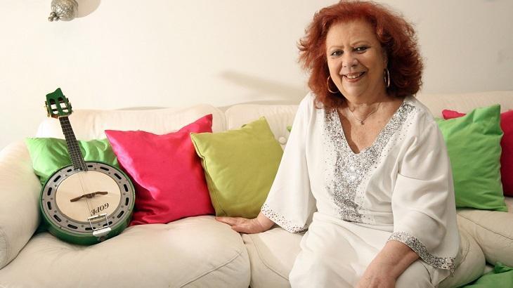 Beth Carvalho, sorrindo, sentada num sofá. Ao lado, um instrumento musical