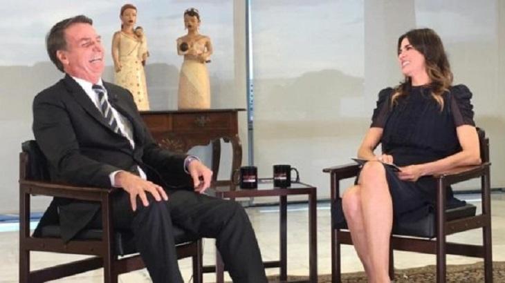 Jair Bolsonaro sentado numa cadeira, ao lado de Luciana Gimenez, também sentada