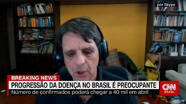 Homem dá entrevista para a CNN Brasil, enquanto ao fundo criança aparece enrolada em toalha do Picachu e usa máscara de herói
