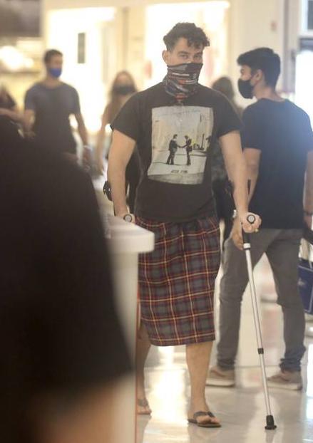 Ator aparece de saia e muletas em shopping do Rio de Janeiro