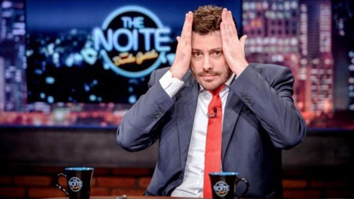 Danilo Gentili com as mãos na cabeça no cenário do The Noite