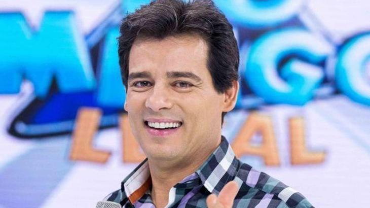 Celso Portiolli posa para foto com o logo do Domingo Legal ao fundo