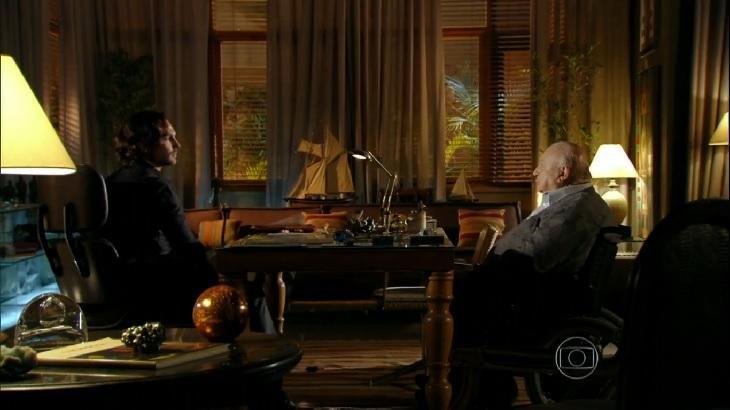 Cena de Flor do Caribe com Alberto e Dionísio conversando sentados frente a frente