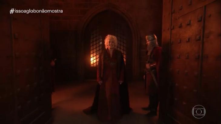 Ana Maria Braga vestindo roupas medievais num cenário que lembra um castelo, ao lado, um guarda.