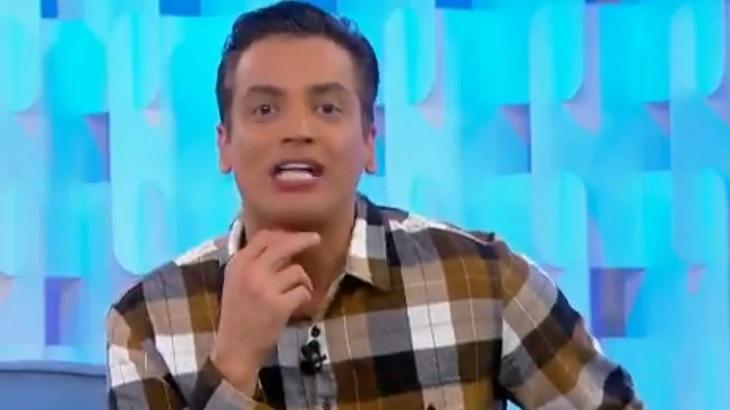 Léo Dias sentado, com a mão no queixo, olha para a câmera