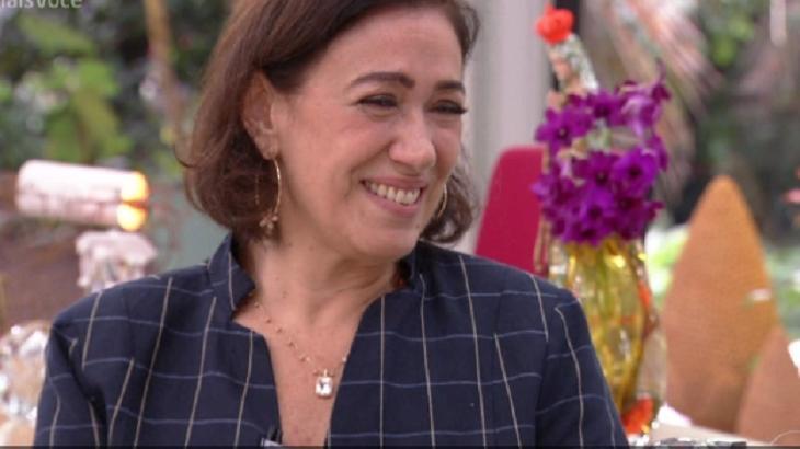"""Lília Cabral sentada à mesa do """"Mais Você"""", sorri emocionada."""