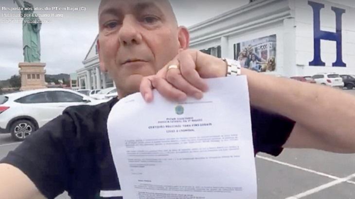 Luciano Hang diante de uma de suas lojas, a Havan, exibe uma certidão