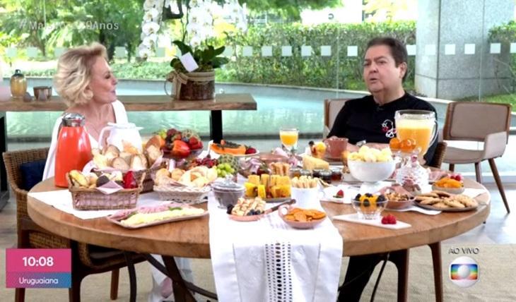 Ana Maria Braga e Fausto Silva sentados diante de uma farta mesa de café da manhã