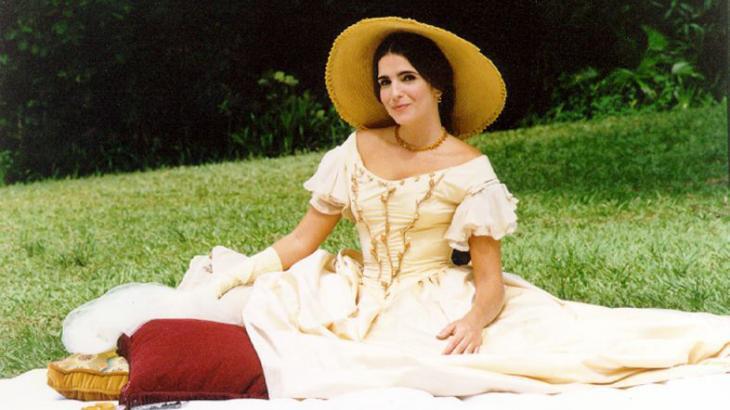 Malu Mader caracterizada como a Baronesa de Sobral, sentada num jardim, numa espécie de piquenique