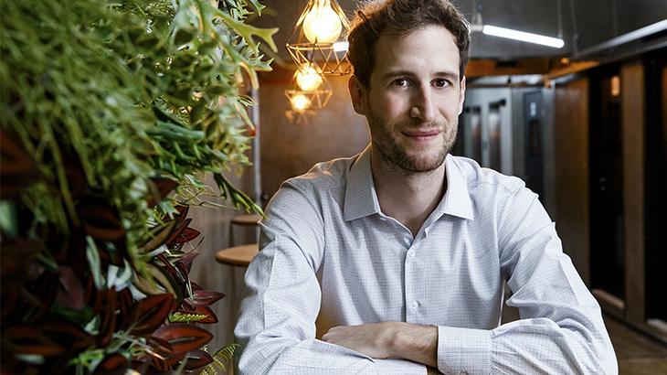 Renato Svirsky, CEO da Guigo TV, de braços cruzados em cima da mesa sorrindo com os lábios fechados
