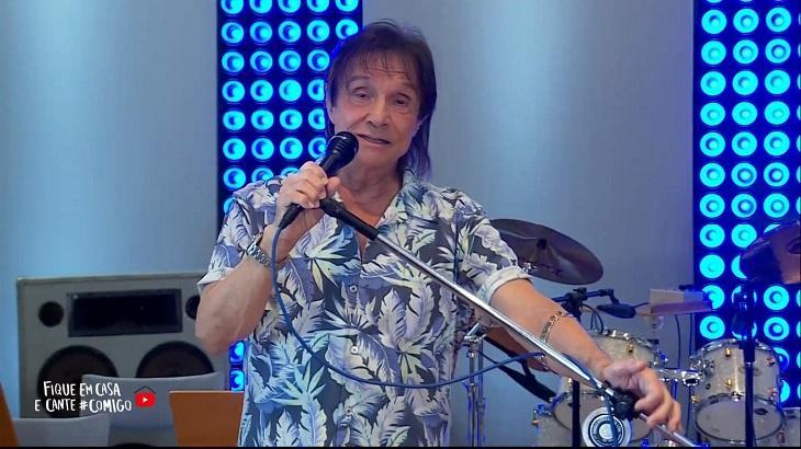 Roberto Carlos cantando com a mão no microfone