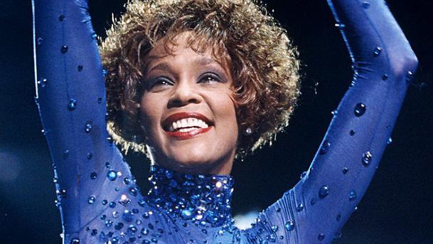 A cantora Whitney Houston levantando as mãos