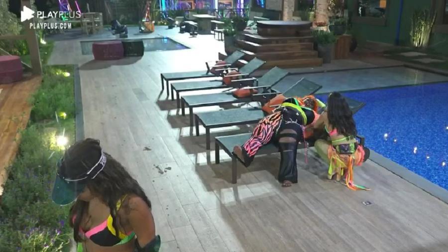 Na área da piscina, Jojo Todynho está deitada na espreguiçadeira e Raissa está ao lado dela em A Fazenda 2020