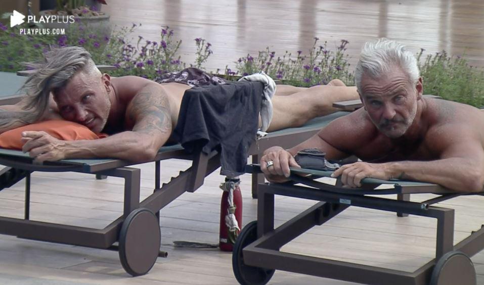 Na beira da piscina, Juliano e Mateus conversam enquanto estão deitados na espreguiçadeira de A Fazenda 2020