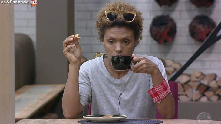 Lidi Lisboa plena, tomando café com biscoito na mão