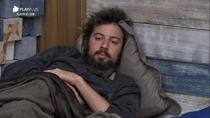 Lucas Cartolouco deitado no quarto olhando para seus colegas de confinamento de A Fazenda 2020