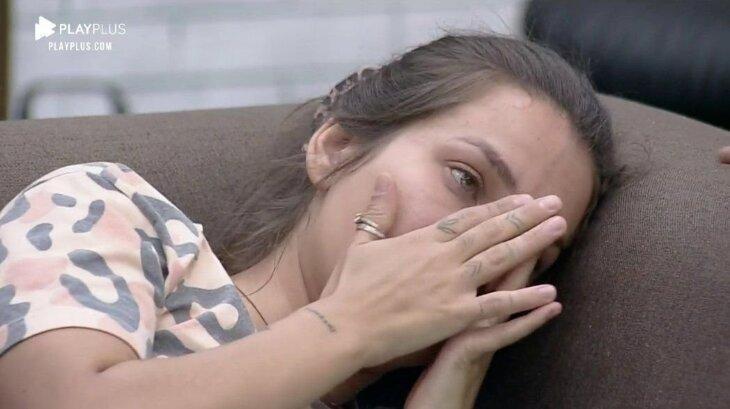 Stéfani Bays chorando no sofá, levando a mão ao rosto