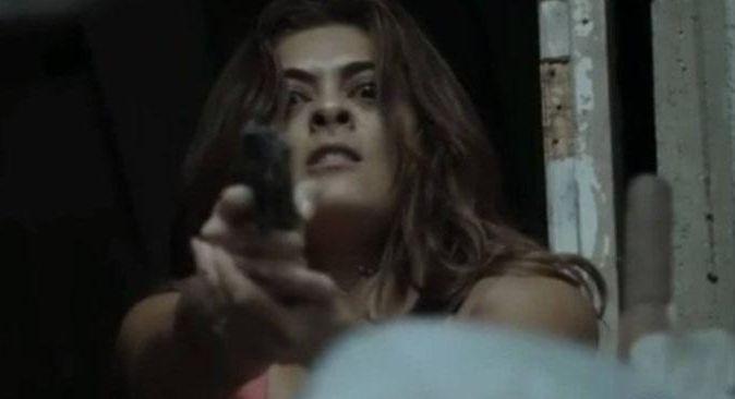 Bibi com expressão de ódio e um revólver na mão