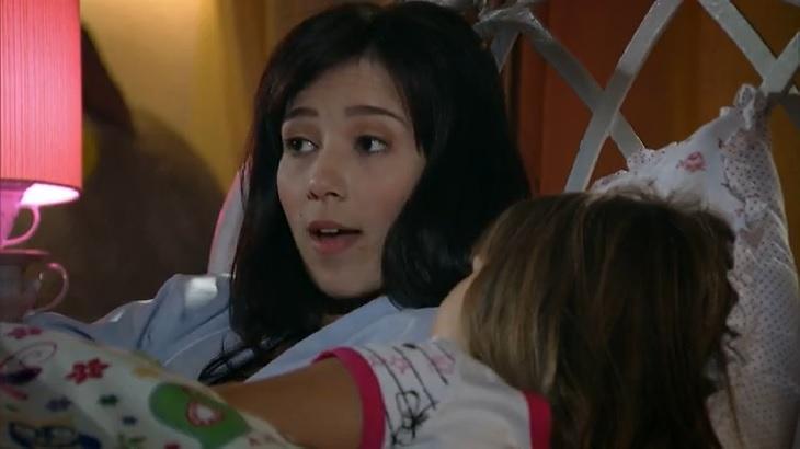 Cena de A Vida da Gente com Manuela deitada na cama conversando com Julia