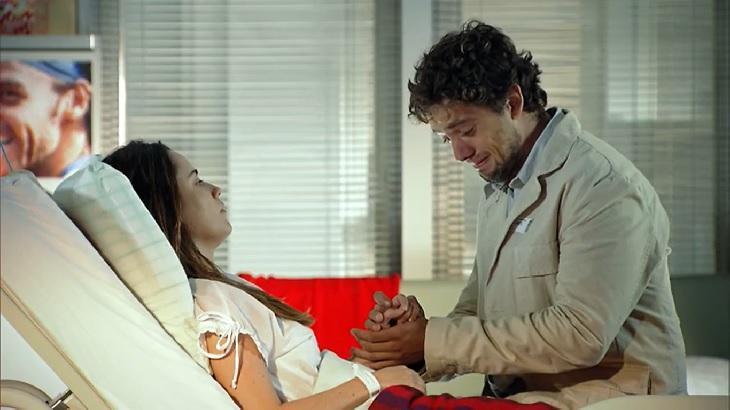Cena de A Vida da Gente com Rodrigo segurando a mão de Ana, que está deitada, e chorando