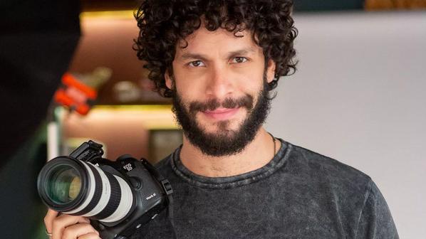 O ator Rainer Cadete com uma máquina fotográfica na mão