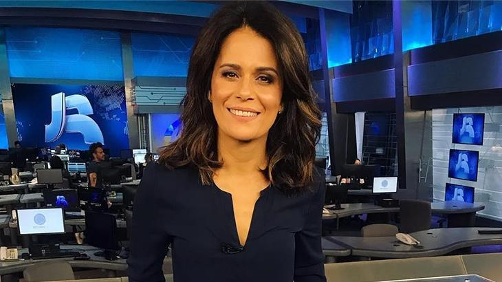Adriana Araújo sorri à frente da bancada do Jornal da Record