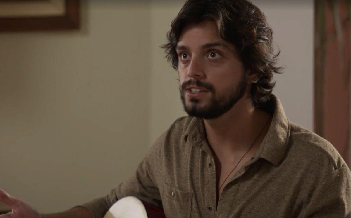 Alejandro sentado com seu violão