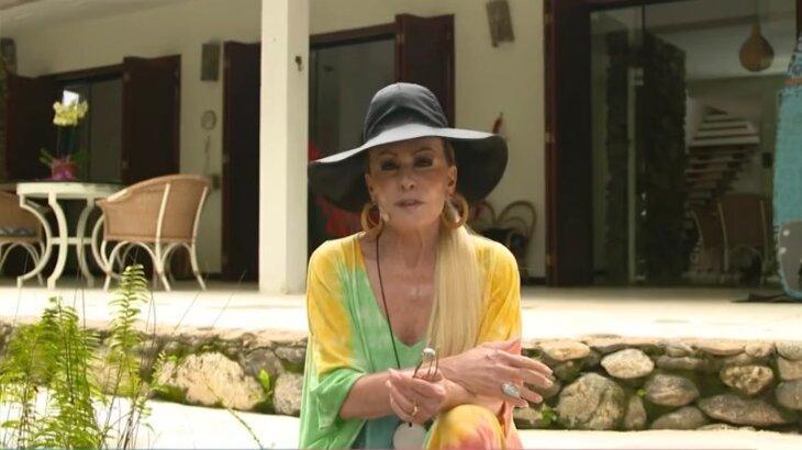 Ana Maria sentada na área externa de casa luxuosa