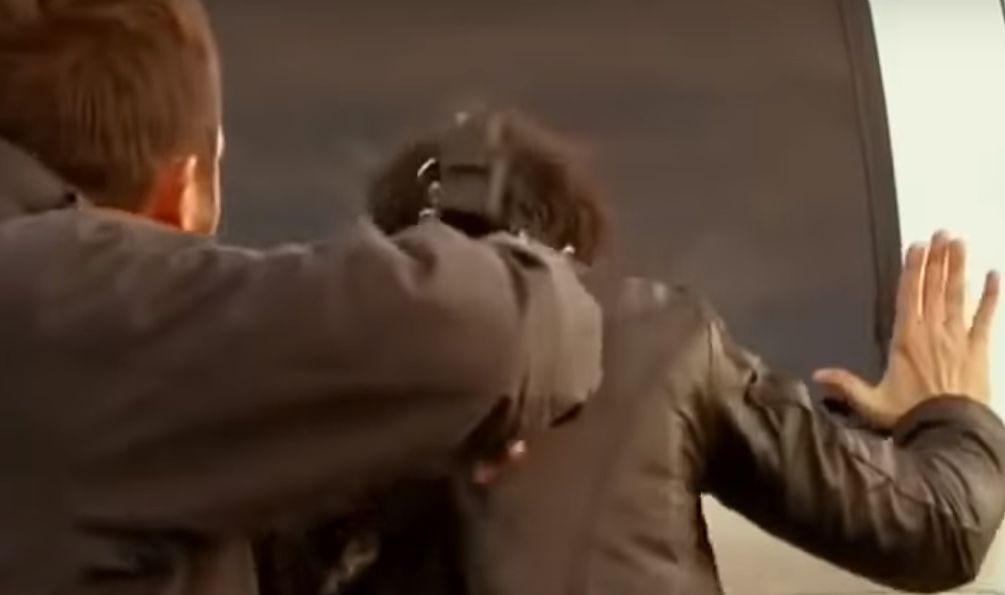 Bandido com arma na cabeça de Aníbal que está de costas com as mãos no carro