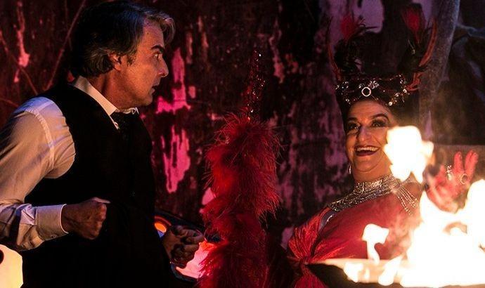 Aparício olha assustado para Teodora que está vestida de diaba e sorrindo