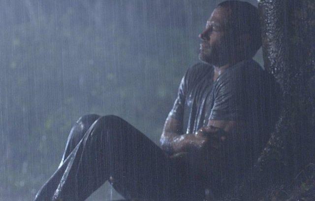 Apolo no meio da noite e debaixo de chuva, sentado encostado a uma árvore