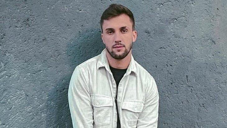 Arthur Picoli posando pra foto com parede cinza