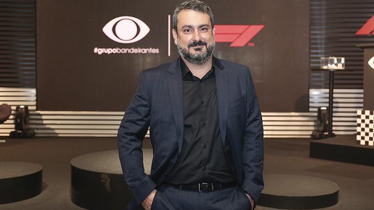 Denis Gavazzi, diretor de esporte do Grupo Band, com terno sem gravata e mão no bolso durante coletiva no canal