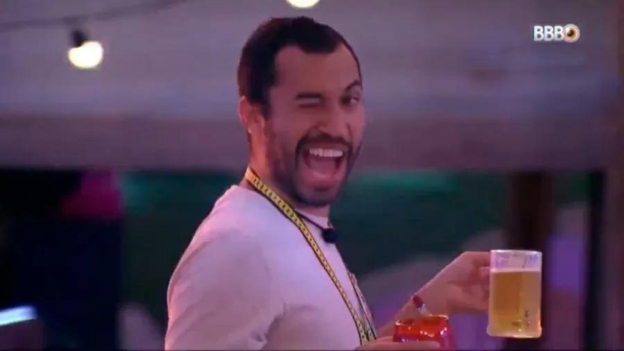Gilberto pisca exageradamente com um copo na mão na festa do BBB21