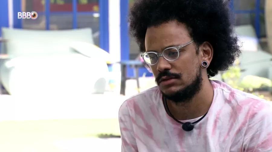 João Luiz está com semblante reflexivo de óculos e blusa branca com detalhes em rosa na área externa da casa do BBB21