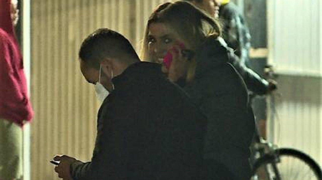 Marcela Queiroz sorridente, sentada e no telefone, enquanto um amigo está a seu lado