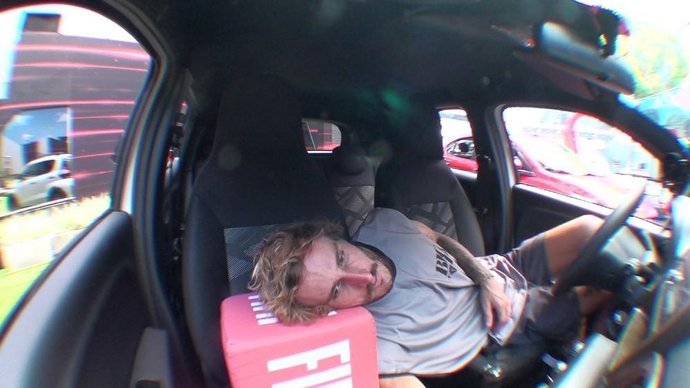 Alan deitado no banco do carro durante a prova