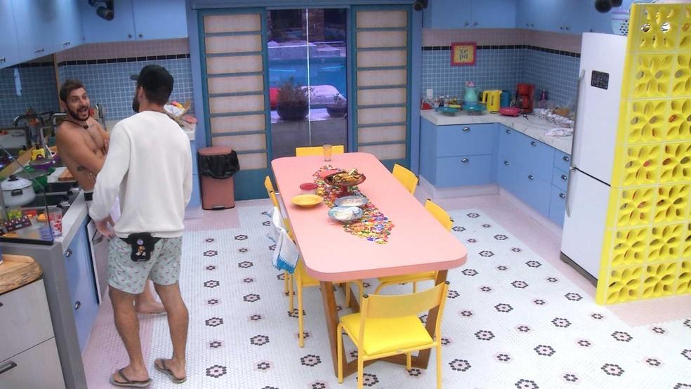 Caio com semblante surpreso está encostado na bancada da cozinha do BBB21 olhando para Arthur que está de costas